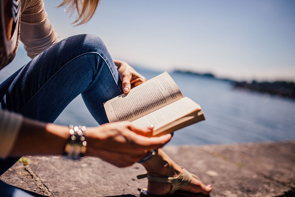 girl reading book at waterside